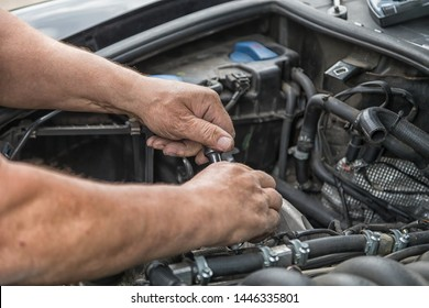Two hands carry out repairs in the engine compartment of a car.