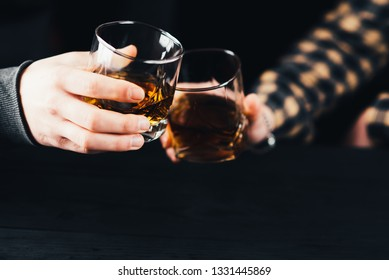 Two hands clink glasses of whiskey on a black background at a black table