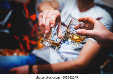 Two hands clink glasses of whiskey at home,on the couch, cozy