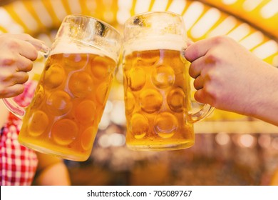 Two hands clinking beer glasses in octoberfest tent