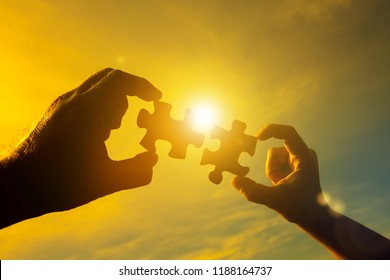 Two hands connect two pieces of the puzzle against the sky and glare of the sun at sunset. Business concept idea, strategy, cooperation, teamwork.