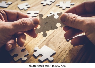 Two hands connect two pieces of the puzzle on a wooden table with many other pieces of the puzzle. Problem Solving Concept.