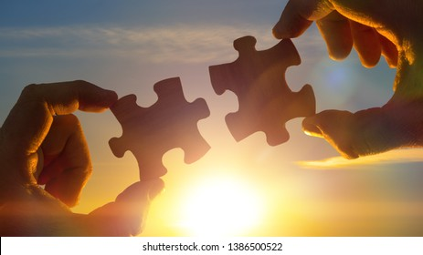 two hands connect the puzzle details, against the sky of the sun. Business concept idea, partner, cooperation, teamwork, innovation.