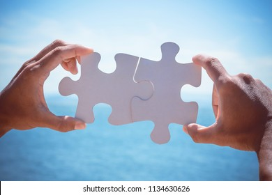 Two hands connect puzzles pieces on sea background. Concept tourism, vacation, sea trip, adventure