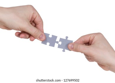 Two hands connecting puzzle pieces. Isolated on white background