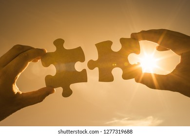 Two hands connecting puzzle pieces together.