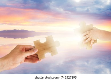 Two Hands Connecting Puzzle Pieces with Dreamy Sunset Background