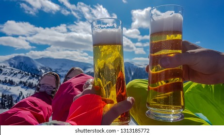Two hands of two different persons, each of them holds a pint of beer. Cheers! Apres ski time. Girl wears pink trousers and the boy wears yellow trousers. Endless chains of mountains. Skiing break.