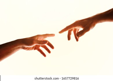 Two hands with fingers that almost touch. Representation of the Christian concept of the creation of man on earth. Horizontal composition