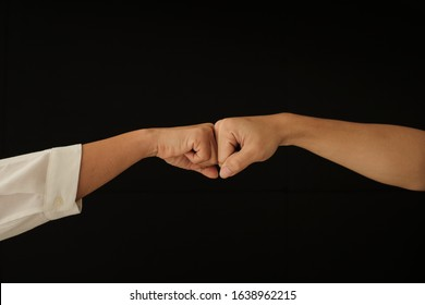 Two hands fistbump together in dark background Friendship, teamwork, respect, commitment, deal concept and symbol