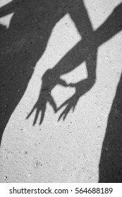 Two hands forming a heart shadow on the asphalt. Black and white photography