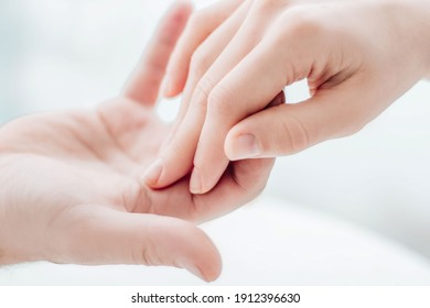 Two hands gently touching each other closeup. Holding hands. Love, skin care, tenderness, relationship, Valentine's day, hands cream, softness, tenderness concept.