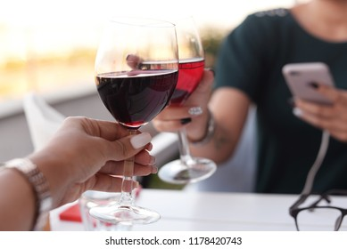 two hands of a girl in a beautiful restaurant at a table holding glasses with a red  of champagne wine at dinner, raising drink  a toast