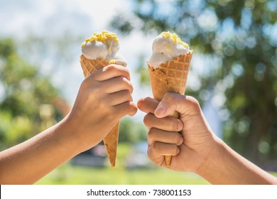 two hands girl holding ice cream cone on summer in light nature background