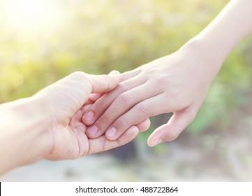 Two hands - helping hand concept against nature background