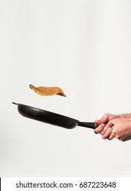 Two hands holding a black pan tossing a pancake in the air against a white background