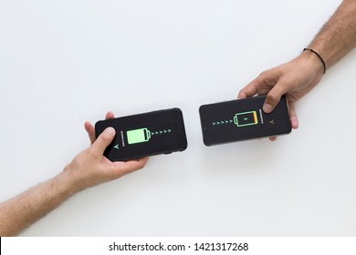 Two hands holding black smart phones while they are wireless charging.Wireless charging of smart phones. They are supplying one another. White background.