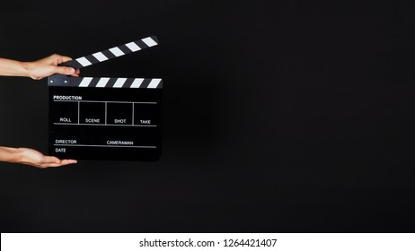 Two Hand's holding Clapperboard or movie slate use in video production ,film, cinema industry on black background.