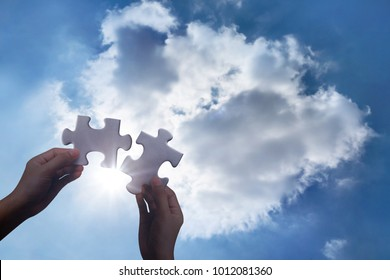 Two hands holding connecting two piece jigsaw heart puzzle at sky clouds background, teamwork concept.