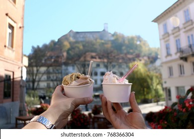 Two hands holding cups with various flavors of ice cream in Ljubljana, Slovenia. Ljubljana Castle in the background.
