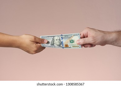 Two hands holding dollar bill. Hands sharing US money. Paying or trading concept.