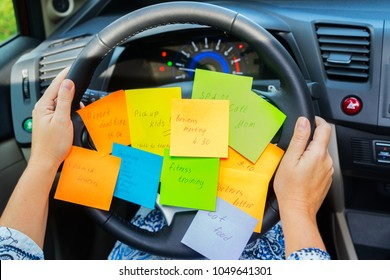 Two hands holding driving wheel and to do list in a car - busy day concept