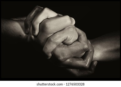 Two Hands Holding Each Other on a Very Strong Grip