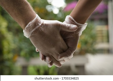 Two hands holding each other wearing sanitary gloves. Close up. Coronavirus concept