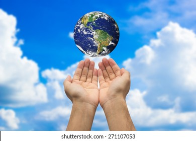 Two hands holding the earth on blurred blue sky background for n take care of world life idea:Elements of this image furnished by NASA