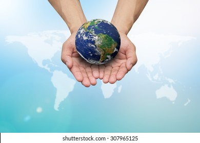 Two hands holding the earth in palm gesture on blurred blue map color gradient background.Elements of this image furnished by NASA