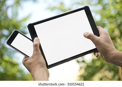 Two hands holding an electronic tablet and a smart phone, both with white screens, for presentation and mock-ups for apps.
