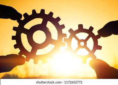Two hands holding gears together. puzzle details on a sunset background. Close-up. Teamwork, partnership, business, cooperation and management concept.