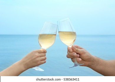 Two hands holding glasses with wine on sea background