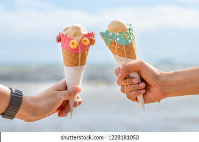 Two hands  holding ice cream cone on the hot summer beach with copy space. Minimal concept. pastel tones.