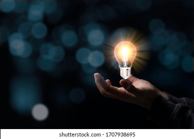 Two hands holding the light bulb that is illuminating. Creative protecting patents and ideas concept.