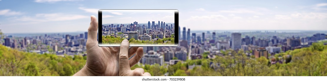 Two hands holding a mobile Smartphone and take a picture of Skyline Panorama from city of Montreal