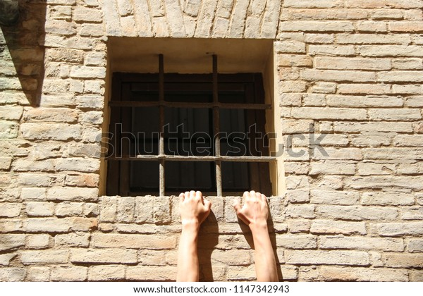 Two hands holding onto a window