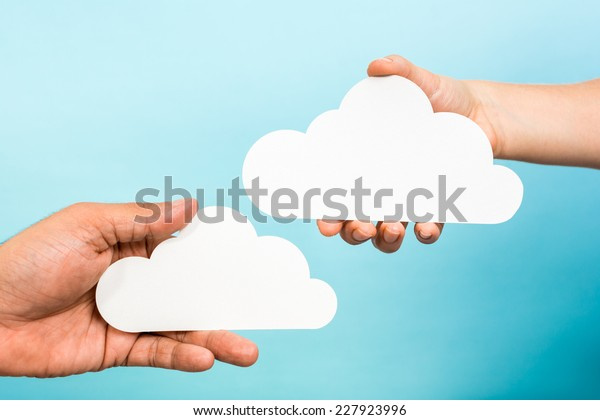Two hands holding paper clouds on blue background. Cloud computing concept.