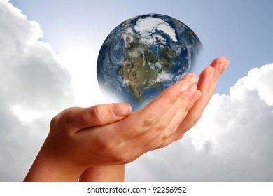 Two hands holding the planet against a blue cloudy sky