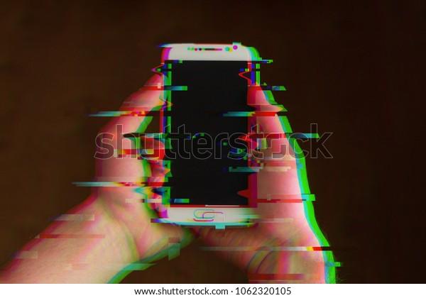 Zwei Hände, die Smartphone halten, Mobiltelefon nach oben, Nahaufnahme. Glitches, verzerrtes, korrumpiertes Bild mit bunten Linien auf dem Telefon und den Händen. Farbkanaleffekt.