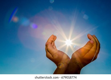 Two hands holding the sun on a blue sky background