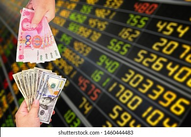 Two hands holding US Dollar and Chinese Yuan banknote on blurred stock market board background