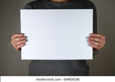 Two hands holding white sheet for copy space