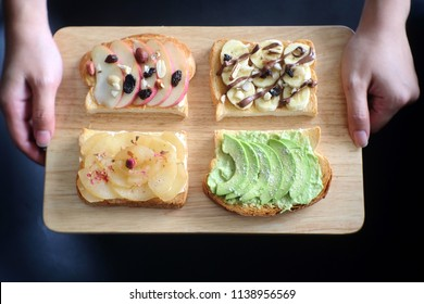 Two hands holding a wooden tray with toast placed. Healthy toast,  healthy breakfast. Selective focus.