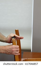 Two hands installing plastic and felt floor protectors on the bottom of a chair leg. Floor protector cups being placed on a chair leg bottom in a dining room.