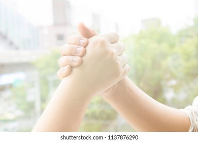 Two hands joining holld together,strong relationship of firends or partnership, trust, teamwork, achievement concept with copy space