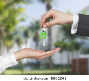 Two hands and a key. Residential area background.
