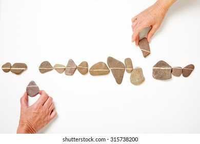 Two hands laying out white line with many stones and pebbles