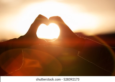 two hands of lover on the background of sunset.Focus on hands.Couple in love.