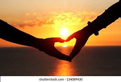 two hands of lovers on the background of sunset on the sea
